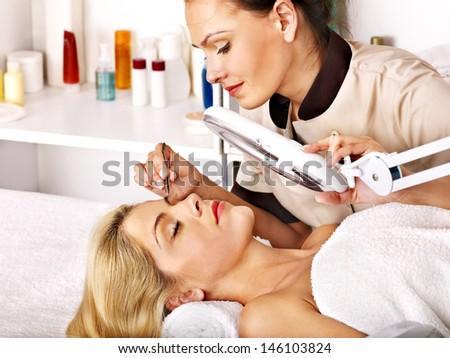 Woman getting tweezing eyebrow. - stock photo