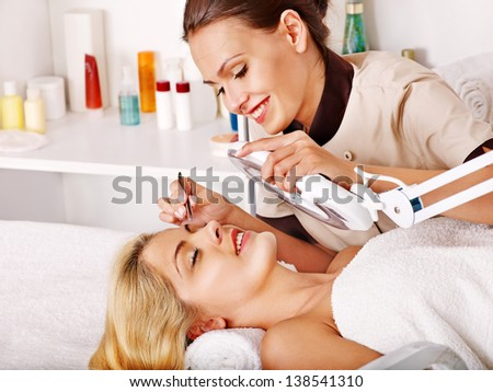 Woman getting tweezing eyebrow by beautician.
