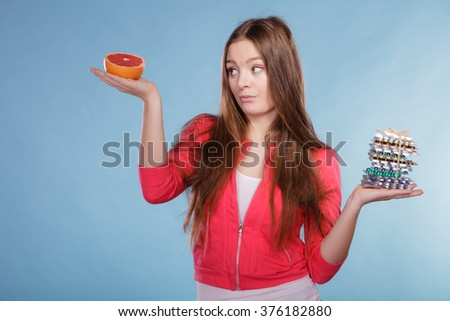 Woman girl holding diet weight loss tablets pills and grapefruit. Choice between natural and synthetic way of slimming dieting. Health care. - stock photo
