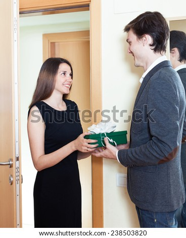 woman gives a beautiful gift to the man at the door - stock photo