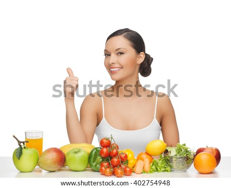 woman gives thumbs up with lot of fruits and vegetables - stock photo