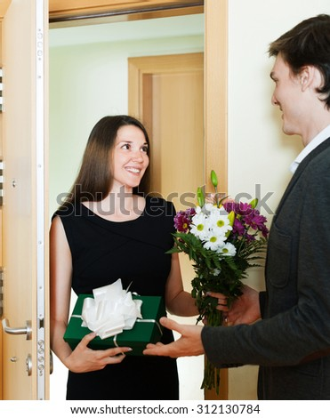 Woman giving a gift to a man on the doorstep