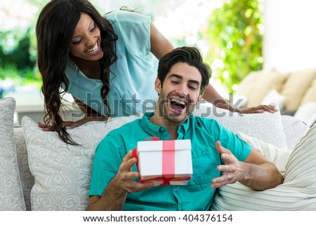 woman giving a surprise gift to man at home - stock photo