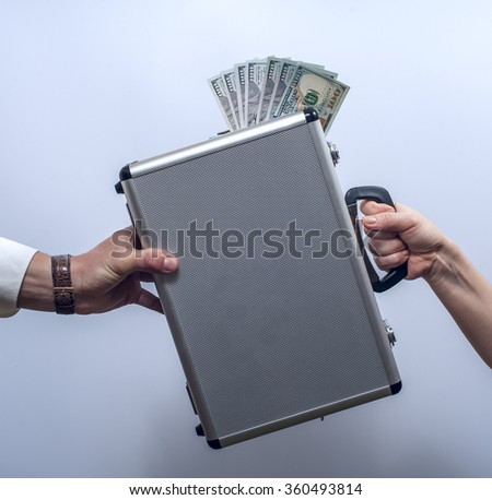 Woman giving briefcase with dollars to man - stock photo