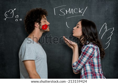 Woman Giving Flying Kiss To Her Boyfriend With Lip Sign On Cheek Over Gray Background - stock photo
