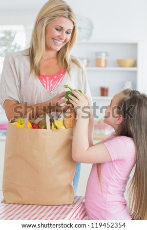 Woman giving green pepper to daughter from grocery bag in the kitchen - stock photo