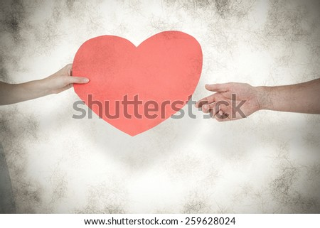 Woman giving heart card to her boyfriend against grey background - stock photo