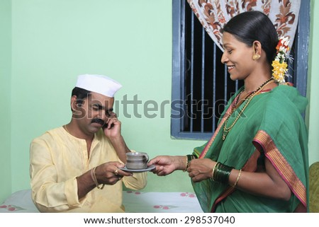 Woman giving her husband a cup of tea - stock photo