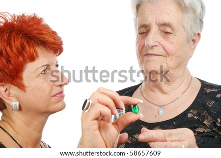 Woman giving medications - drugs and vitamins - to an elderly woman. - stock photo