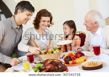 Woman giving salad to her daughter - stock photo
