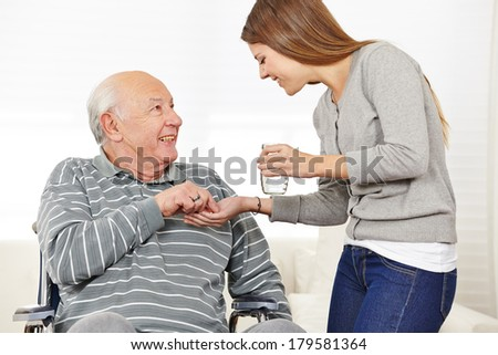 Woman giving senior man in wheelchair medical pill with a glass of water - stock photo