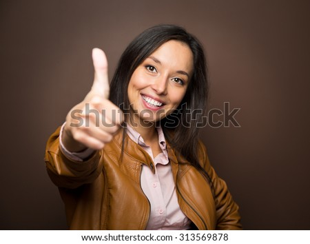 Woman giving thumbs up approval hand sign gesture smiling happy isolated on white background in full body length in high angle perspective view. Content smile on multiracial asian caucasian woman. - stock photo