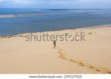 Woman goes down the Great Dune of Pyla, Arcachon (France) - stock photo