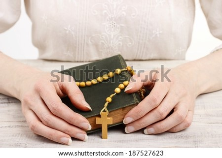 Woman golding wooden rosary and Holy Bible.