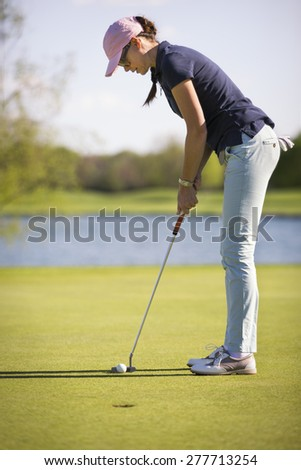Woman golf player concentrating for putting on green, with lake in background. - stock photo