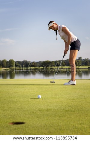 Woman golf player putting ball on green. Golf ball rolling towards cup. - stock photo