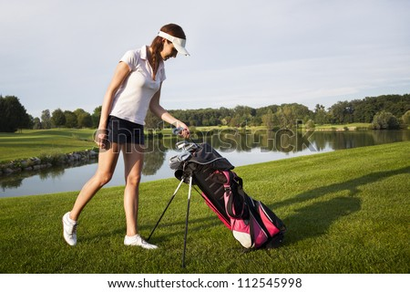 Woman golf player taking out golf club from golf bag on golf course with beautiful pond and trees in background.