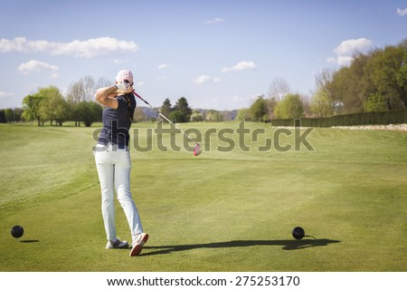 Woman golf player teeing off ball. - stock photo