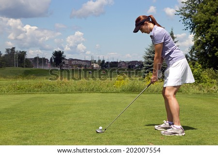 Woman golfer with a golf club on the tee box - stock photo