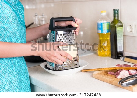 Woman grating a wedge of cheese for a recipe to be added to the raw chopped meat standing ready on the kitchen counter as she cooks the evening meal - stock photo