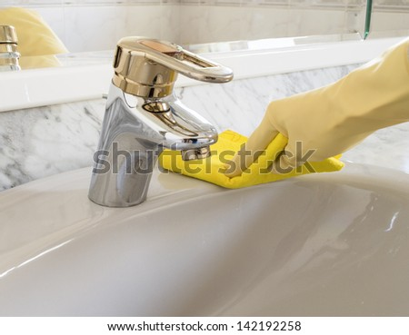 woman gray sink cleaning with yellow gloves - stock photo