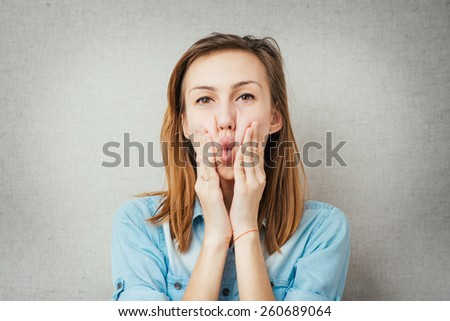 woman grimace hands on cheeks. isolated on gray background - stock photo