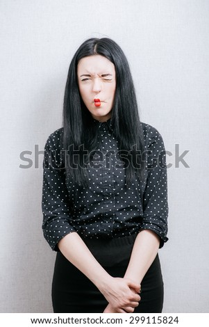 Woman grimace on her face. On a gray background. - stock photo