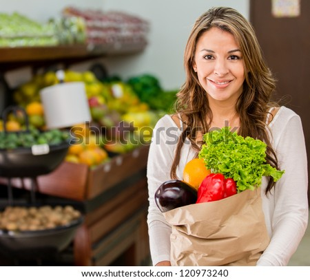 Woman grocery shopping at the local market - stock photo