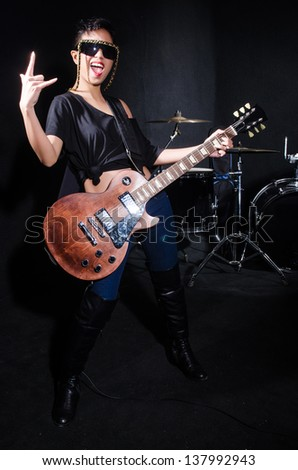 Woman guitar player during concert