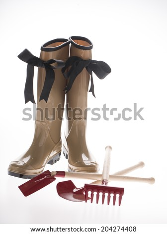 woman gum boots with garden tools - stock photo