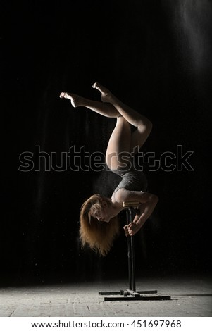 Woman gymnast handstand on equilibre at black background - stock photo