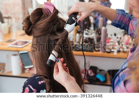 Woman hairdresser making hairstyle using curling iron for long hair of young female with smartphone in beauty salon - stock photo