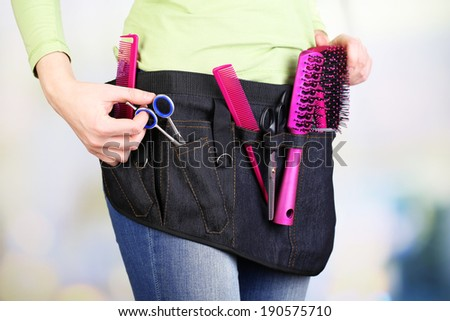 Woman hairdresser with tool belt on bright background - stock photo