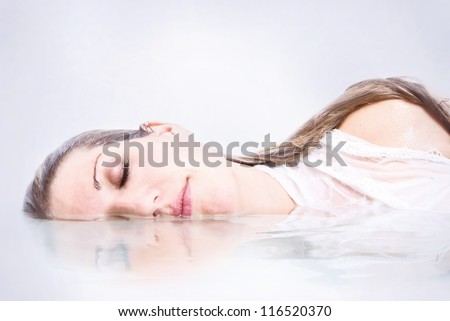 Woman half submerged in water with reflection - stock photo