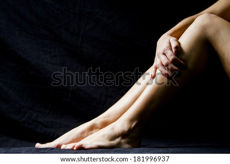 Woman hand and legs with dark background