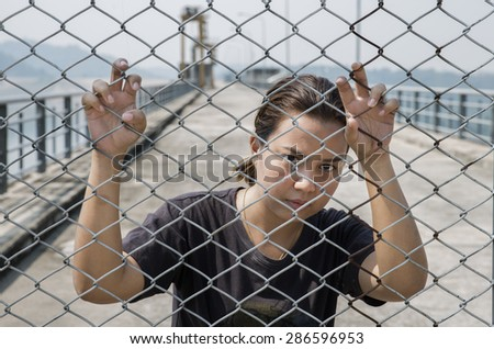 woman hand and steel cage on the evening light, concept of the freedom