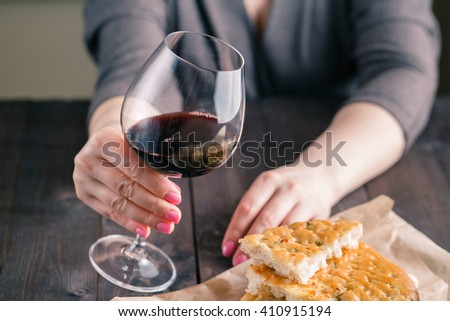 Woman hand and wineglass on kitchen with bread