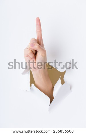 Woman hand breaking through paper wall with finger point up