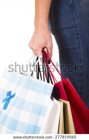 Woman hand carrying a bunch of shopping bags isolated on white - stock photo