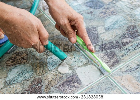 woman hand cleaning floor tiles using brush
