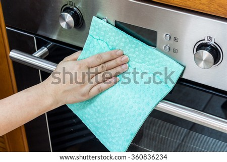 Woman hand  cleaning oven at home kitchen - stock photo
