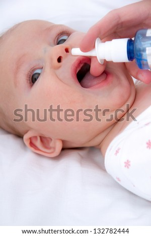 woman hand cleans baby's nose
