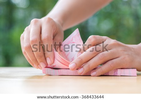 Woman hand counting thai cash on wood table - stock photo