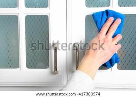 Woman hand doing chores in the kitchen at home , cleaning kitchen dresser - stock photo