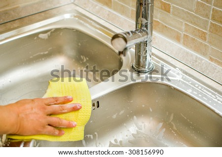 Woman hand doing chores in the kitchen at home , cleaning sink and faucet with a yellow sponge - stock photo