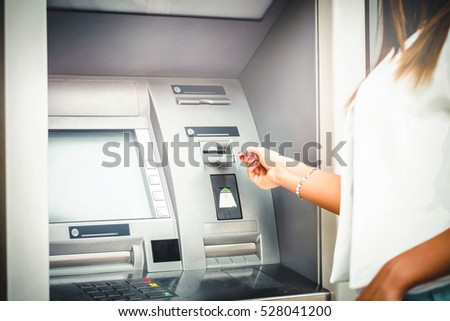 Woman hand enter number on atm machine