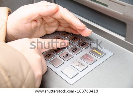 woman hand entering pin code in a ATM - stock photo