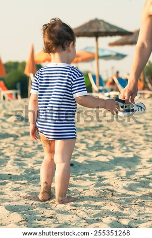 Woman hand giving flip flops to a toddler with sailor shirt on a beach. Photo with untraditional color rendering for artistic look - stock photo
