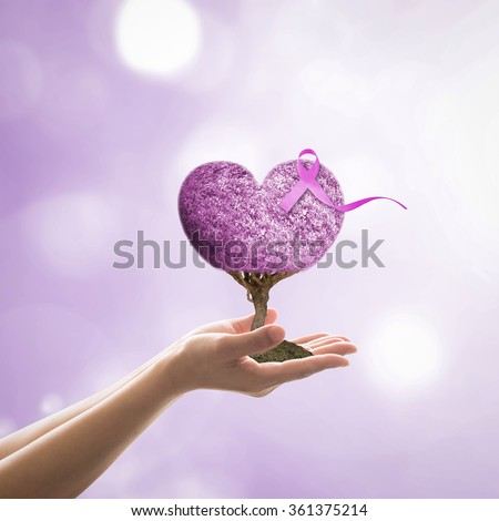 Woman hand giving lavender purple color heart shaped love living tree of life w/ symbolic ribbon awareness on periwinkle background: World cancer day (all kind tumors): National cancer survivors month - stock photo