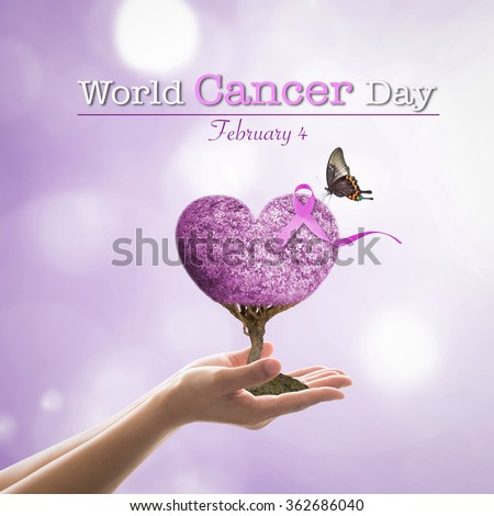 Woman hand giving purple color heart shaped tree of life w/ symbolic ribbon & living butterfly on lavender background: World cancer day raising awareness all kind concept to support people w/ illness - stock photo